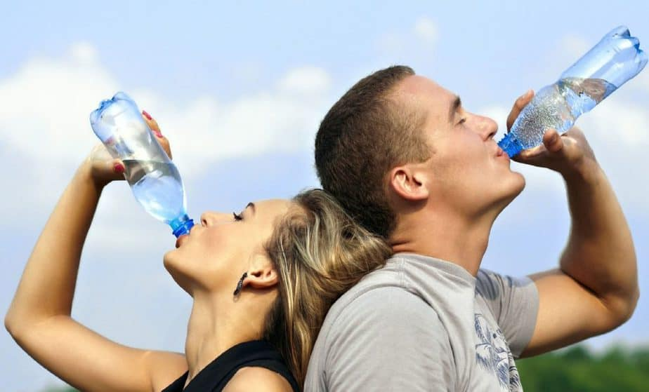 a young couple drinking water to stay hydrated