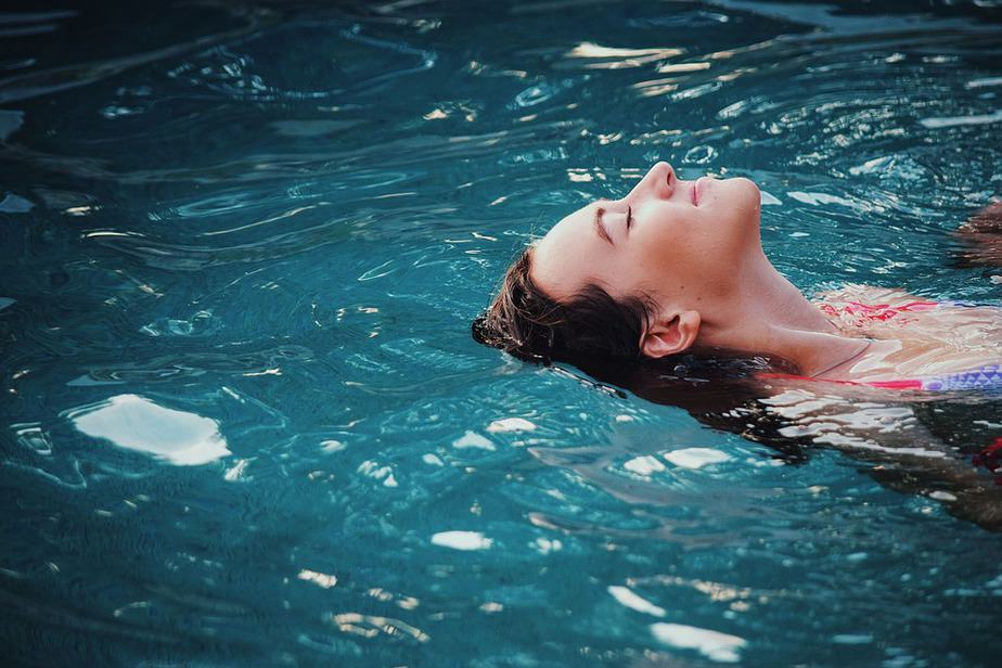 a girl swimming and relaxing in the pool, health and wellness