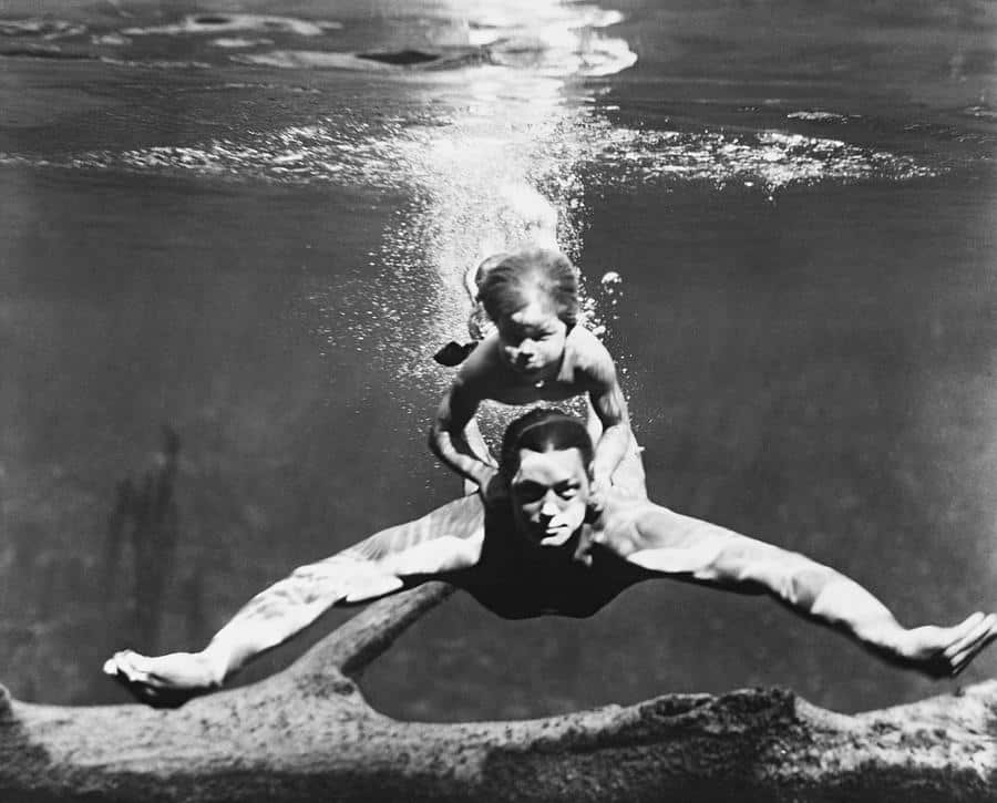 Johnny Weissmuller professional swimmer and actor, swimming with a child