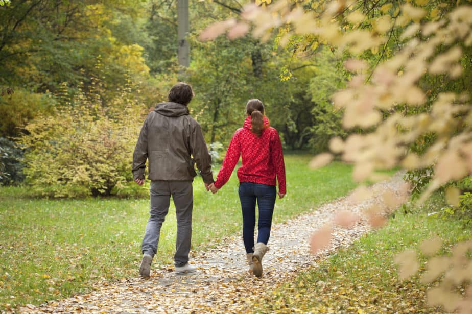 A young couple takes a walk through the park covered with leaves