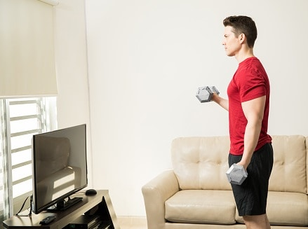A guy has a weightlifting training session at home in front of TV