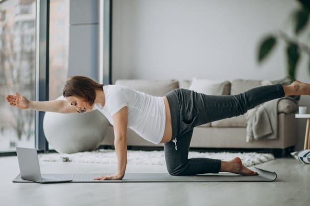 A pregnant woman exercising at home