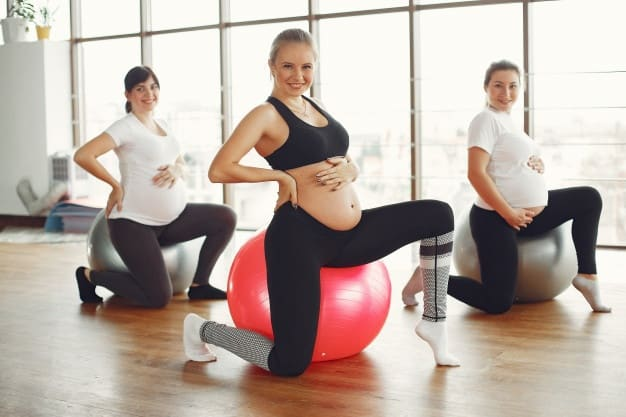 A pregnant women working out on yoga balls