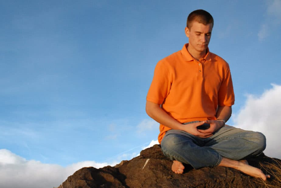 zen meditation - a man meditating outside