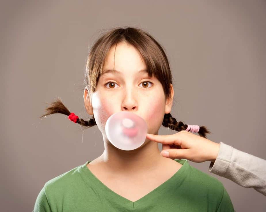 A young girl is chewing a bubblegum