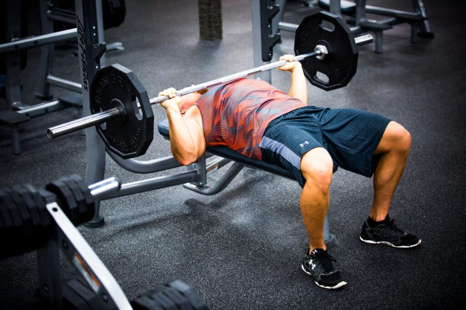 A guy has a training with weights at the gym