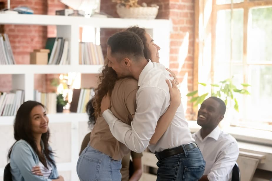 people hugging in a group therapy