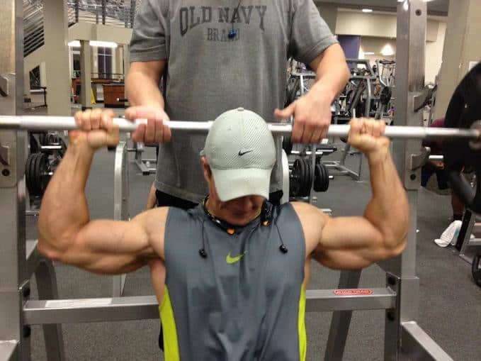 A guy has a training with a barbell behind his neck at the gym