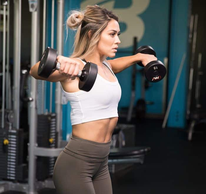 A girl has a training for building up her shoulders