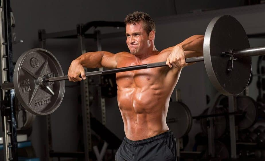 A guy has a training with the barbell at the gym