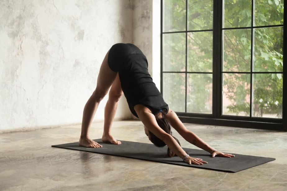 A young woman practicing yoga in a Adho mukha svanasana  pose