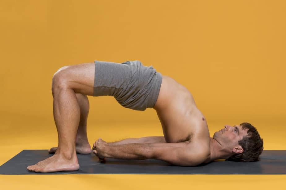 A young man is practicing yoga doing Setu Bandha Sarvangasana pose