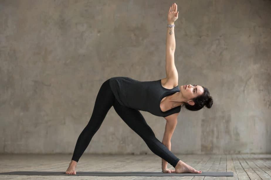 A young woman doing yoga in a Utthita Trikonasana pose