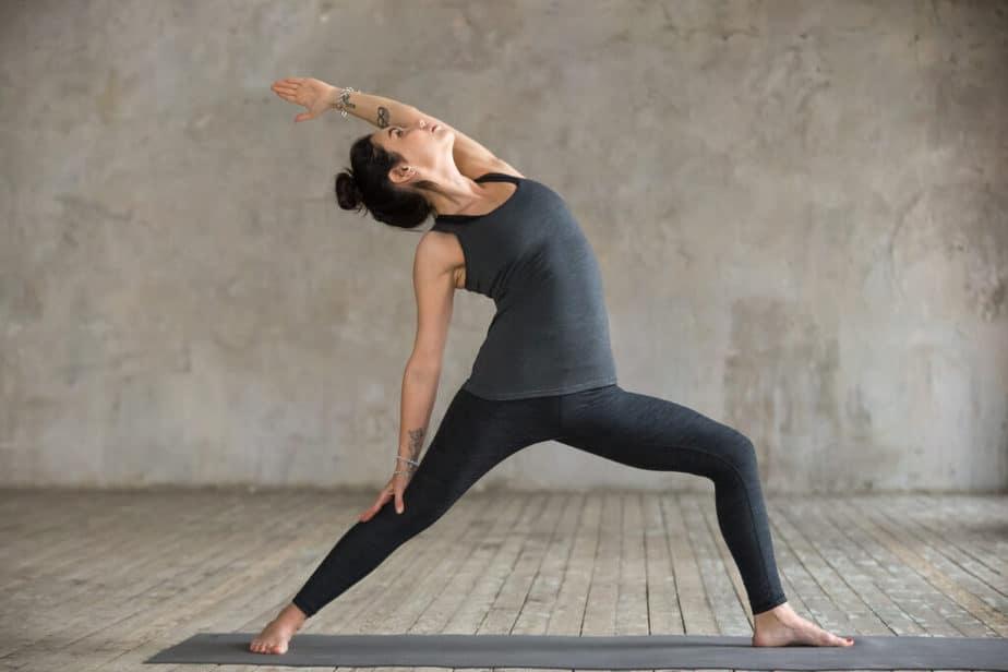 A girl is practicing yoga in a Viparita Virabhadrasana pose