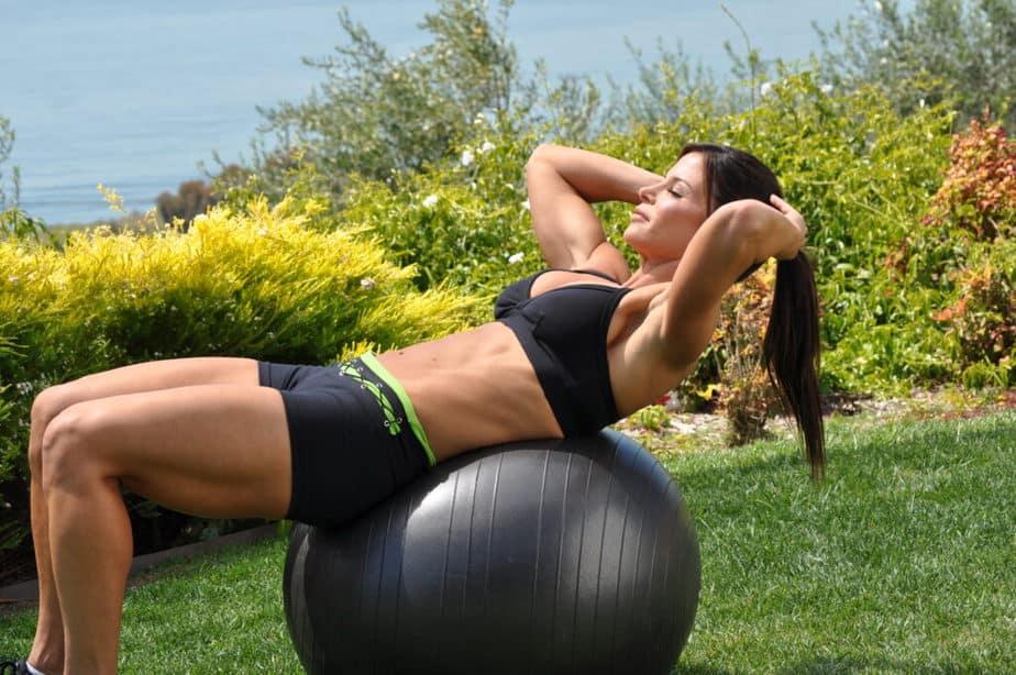 A girl has a training on gym ball