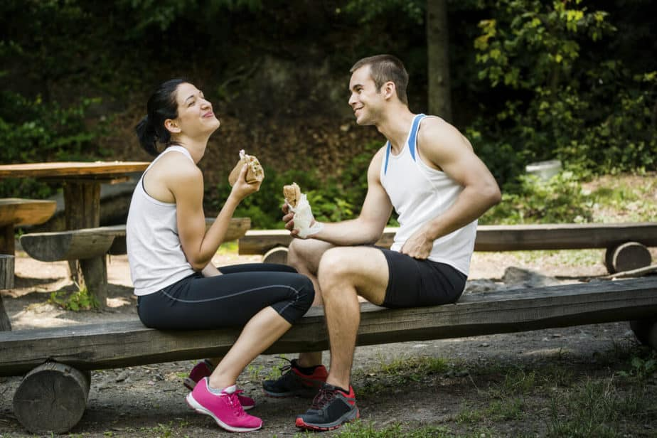 A young couple is having a breakfast brake, after training, at the park
