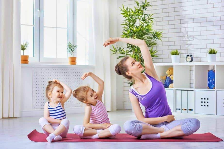 A young mom is playing and doing exercises with her kids at home