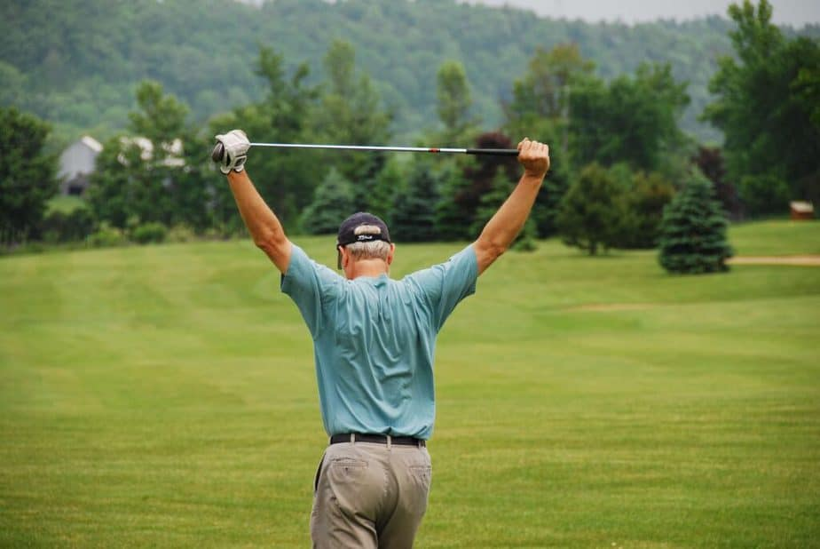 A golfer is stretching his shoulders