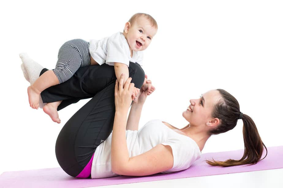 A young mother has a workout at home with her baby