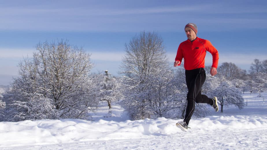 A guy is exercising on the snow