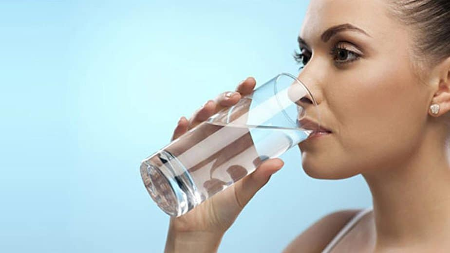 a young woman maintaining balance in her life by drinking water and staying hydrated