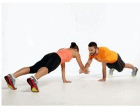A couple is doing plank claps push ups.