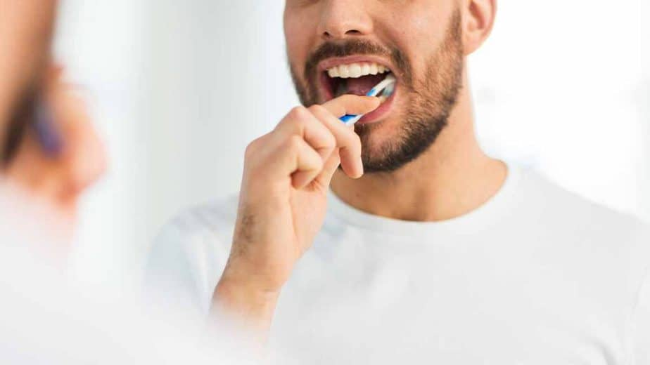 A guy is brushing his teeths