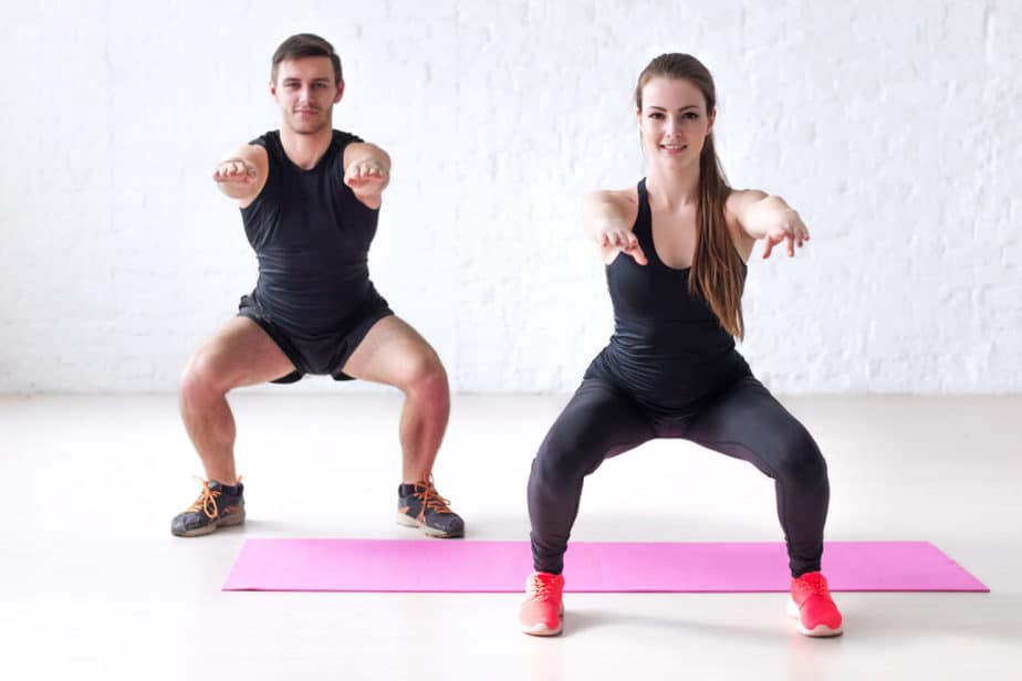 A couple is doing exercise with semi high knees.
