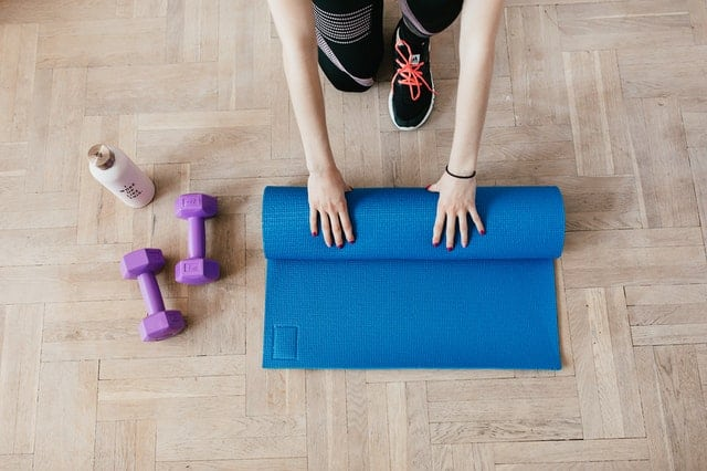 An exercise mat and dumbbells, important additions to a budget home gym.