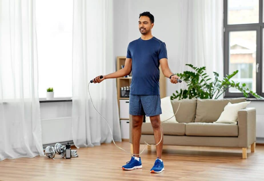 A guy has a training with jump rope at home