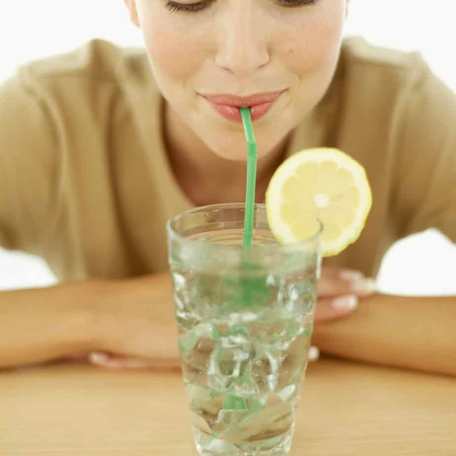 A girl is drinking water with straw, while training lungs.