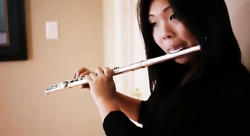 A girl is playing a flute and has a lung training.