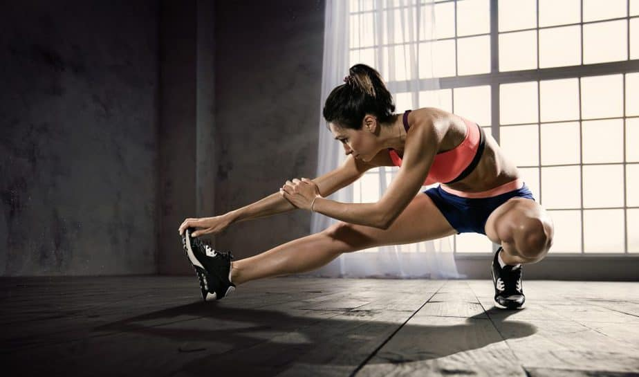 A girl is stretching before her training, to avoid fitness mistake.