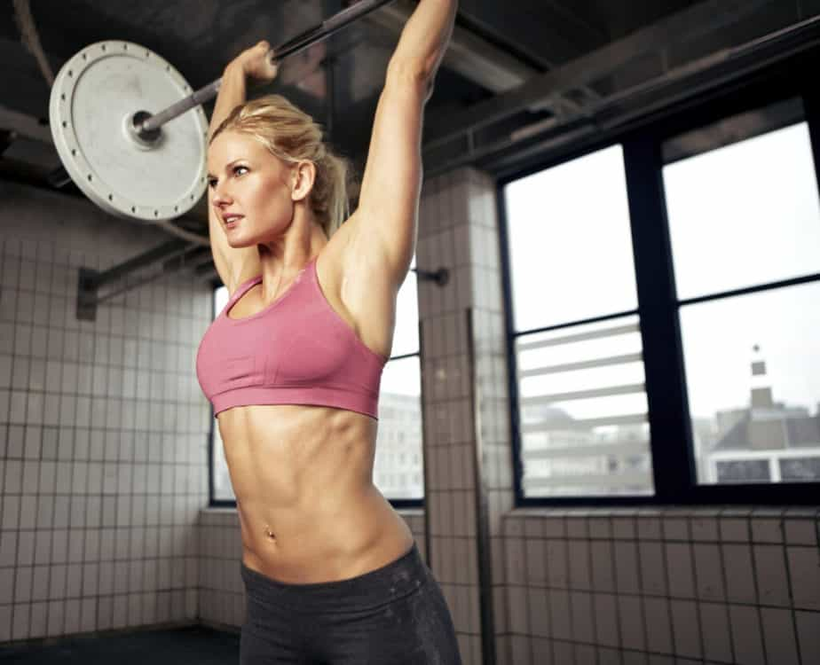 Woman doing shoulder press exercise with a weight bar over head.