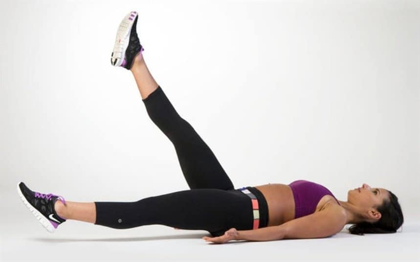 A girl is raising her legs alternately lying on the back.
