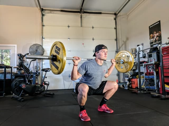 A guy lifting weights at the home gym - garage.