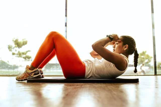 A girl is doing crunches at home gym.