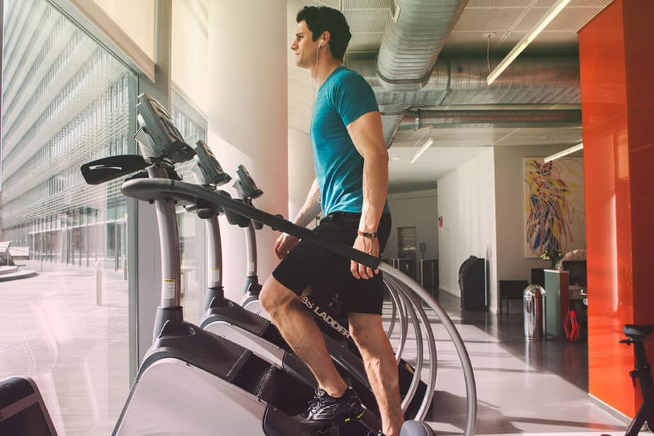 A guy has a cardio workout at the machine in the gym.