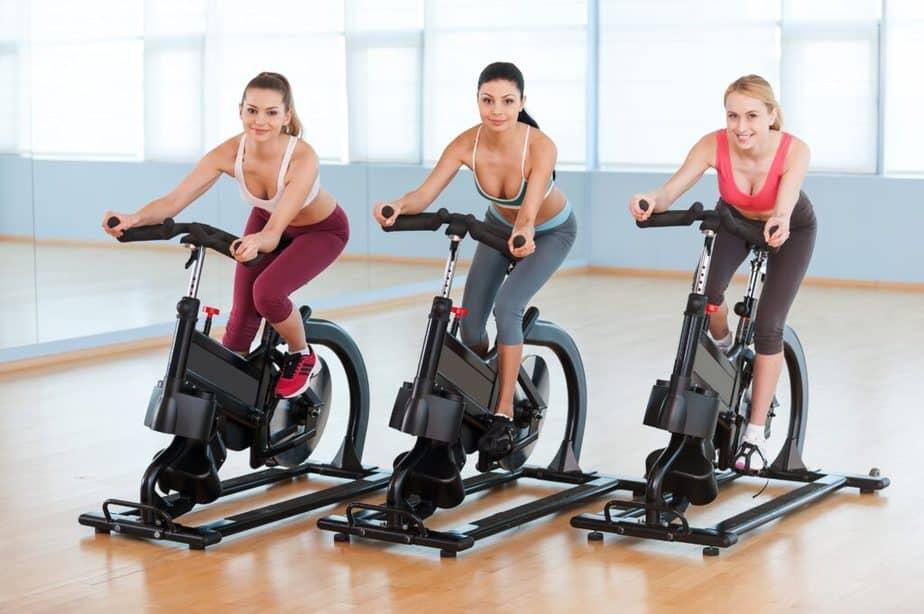 Three girls have training on cardio machines - ellipticals.