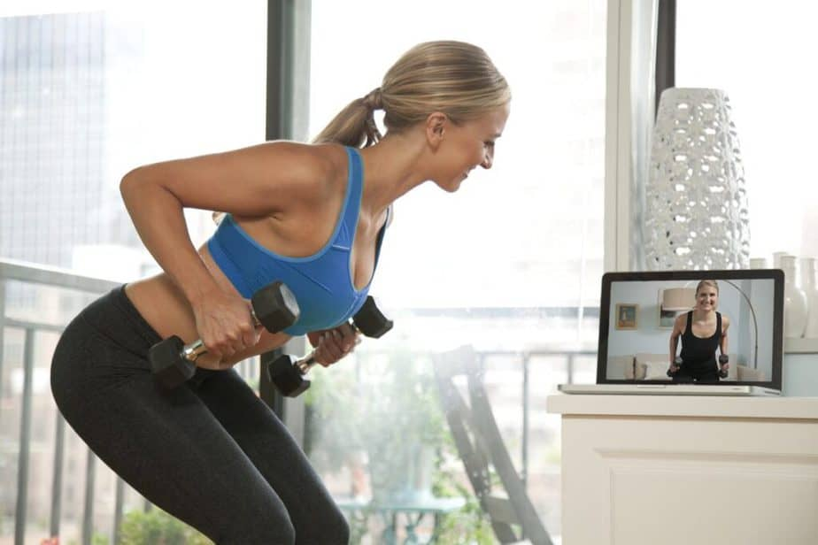 A girl has a online training - latest fitness trend.