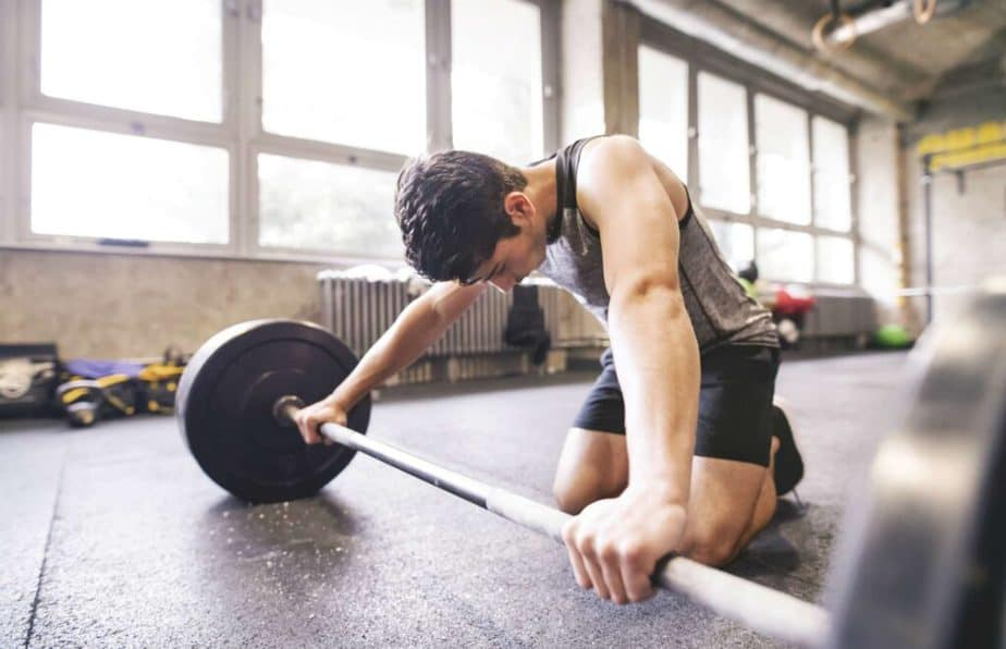 An example of cardio training mistake - a tired guy is preparing to lift weights.