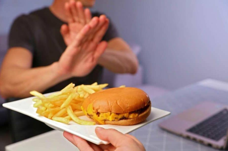 A guy is controlling his hunger by rejecting greasy food.