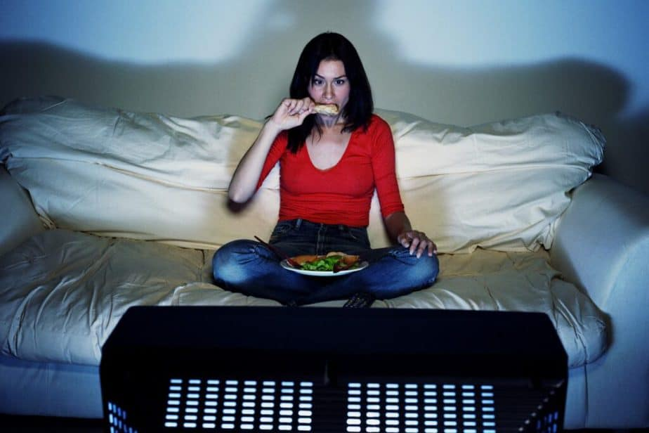 A girls is eating in front of TV.