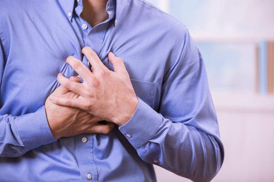 Adult man clutching his chest in pain with a possible heart attack.