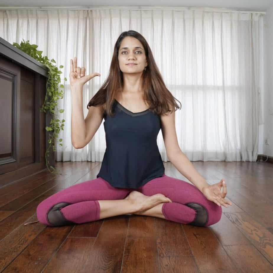 a girl is in a quarter lotus meditative pose.