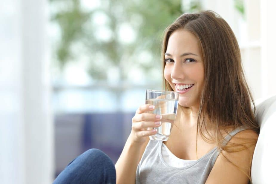 A girl is drinking water. It helps to reduce weight.