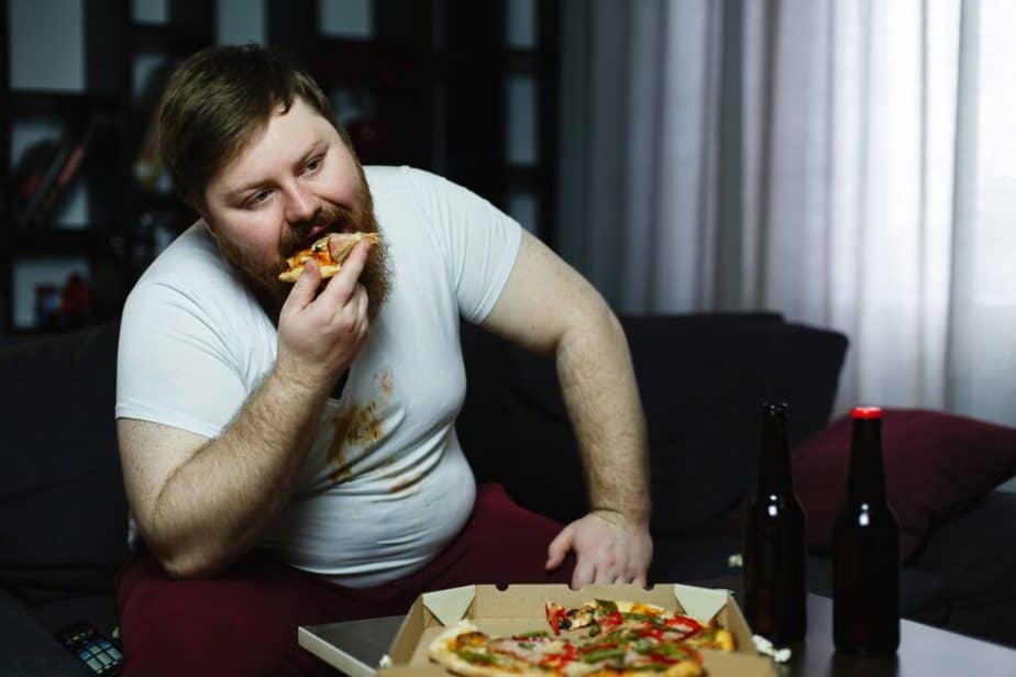 A fat man eating pizza.