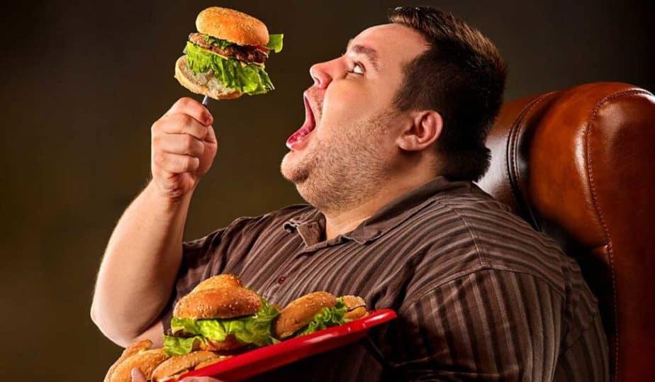 Fat guy eating burgers.