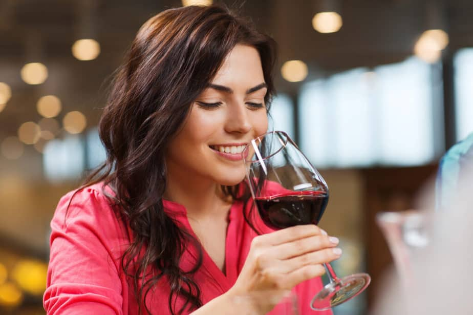 A young woman is drinking red wine.