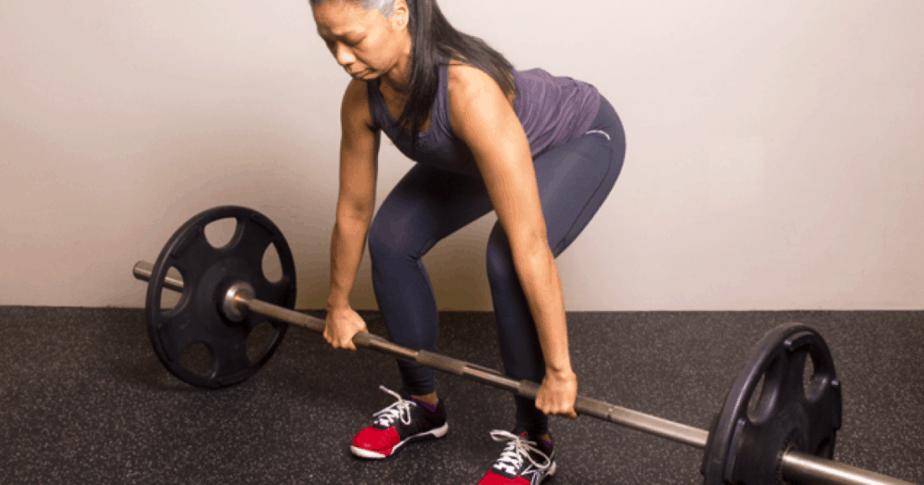 A girl is having deadlift exercise for tight butt.